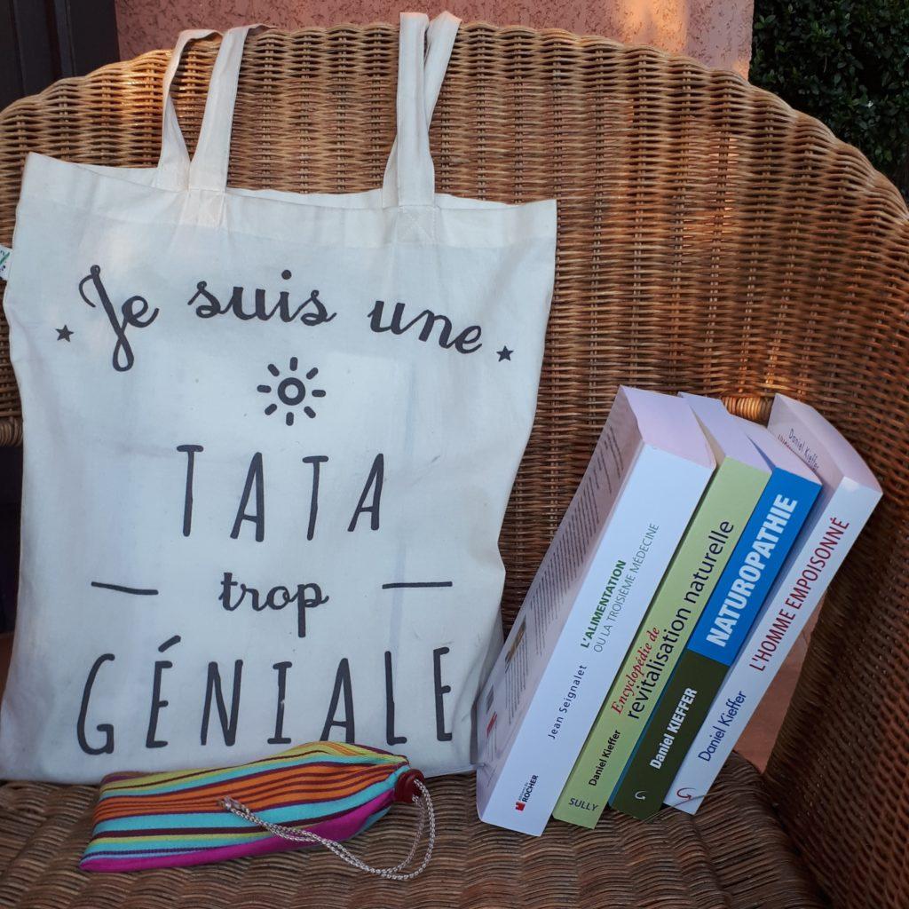 """Photo de mon sac, sur lequel il est écrit """"je suis une tata trop géniale"""", accompagné de ma trousse en tissu rayé faite maison et de 4 livres sur la naturopathie."""