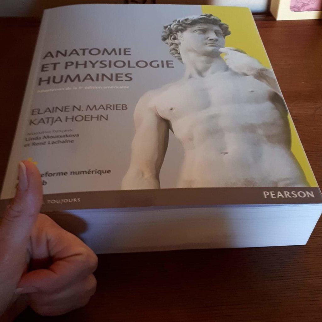 """Photo du livre """"Anatomie et physiologie humaines"""" de Elaine N. Marieb et Katja Hoehn. Avec devant mon pouce levé, pour se rentre compte de l'épaisseur de l'ouvrage."""