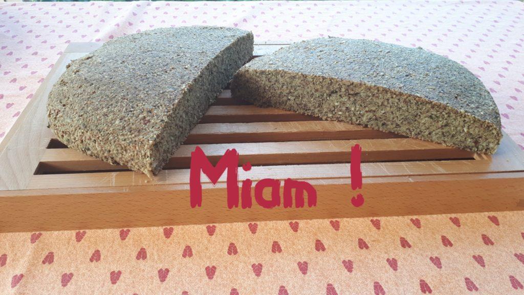 """Photo du grain aux graines, coupé en deux, sur une planche à pain. Avec en texte """"Miam !""""."""
